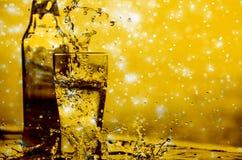 Chapoteo de la cerveza con el bokeh del brillo de la estrella, la Navidad y el conce del Año Nuevo Imágenes de archivo libres de regalías