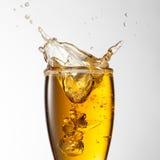 Chapoteo de la cerveza en el vidrio aislado en blanco Imagen de archivo