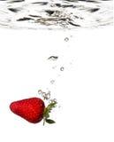 Chapoteo de la fresa en agua fotos de archivo