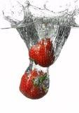 Chapoteo de la fresa en blanco Imagen de archivo libre de regalías