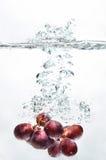 Chapoteo de la fruta de la uva en el agua Imagen de archivo
