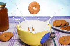 Chapoteo de la leche con las galletas imagenes de archivo