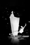 Chapoteo de la leche en fondo negro Fotos de archivo libres de regalías