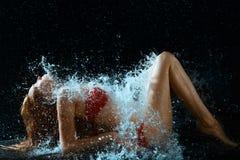 Chapoteo de la mujer y del agua en oscuridad Imagen de archivo