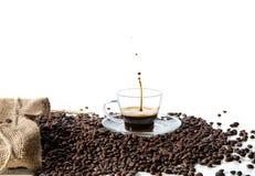 Chapoteo de la taza del café express sobre habas en blanco Imágenes de archivo libres de regalías