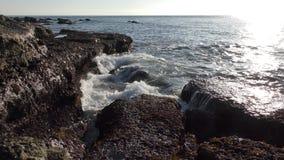 Chapoteo de las ondas del mar en rocas de la orilla almacen de metraje de vídeo