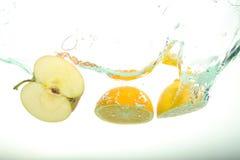 Chapoteo de las rebanadas de dos, del limón y de la manzana del agua en el fondo blanco fotos de archivo