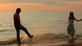 Chapoteo de los recienes casados en la playa almacen de video