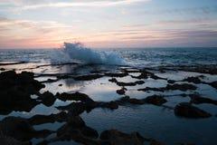 Chapoteo de olas oceánicas contra un fondo de la puesta del sol y de rocas imagen de archivo