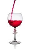 Chapoteo de un vino rojo en vidrio imágenes de archivo libres de regalías