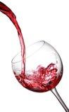 Chapoteo de un vino rojo en vidrio fotografía de archivo