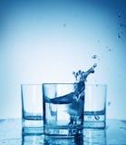 Chapoteo del agua en un vidrio Foto de archivo libre de regalías