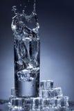 Chapoteo del agua en un vidrio. Fotos de archivo