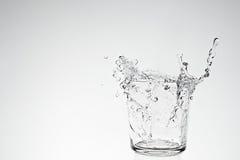 Chapoteo del agua en vidrio de consumición Fotografía de archivo libre de regalías