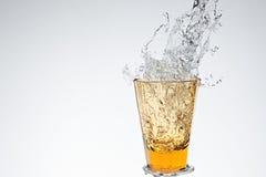Chapoteo del agua en vidrio de consumición amarillo Imágenes de archivo libres de regalías