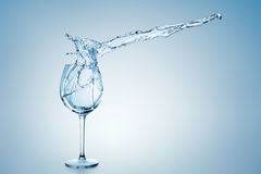 Chapoteo del agua en vidrio de vino imagen de archivo
