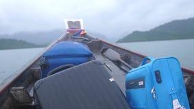 Chapoteo del agua a lo largo del lado el barco de madera turístico rápido con una maleta en el tiempo nublado, Tailandia Cámara l almacen de metraje de vídeo