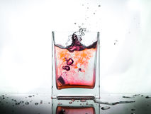 Chapoteo del agua roja en el vidrio aislado en el fondo blanco Foto de archivo