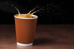 Chapoteo del café en taza imágenes de archivo libres de regalías
