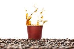 Chapoteo del café en taza de papel disponible marrón con los granos de café aislados en blanco imagenes de archivo