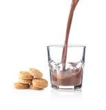 Chapoteo del chocolate en un vidrio con las galletas Foto de archivo libre de regalías