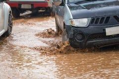 Chapoteo del fango por un coche como pasa a través del agua de inundación Imagen de archivo