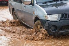 Chapoteo del fango por un coche como pasa a través del agua de inundación Fotos de archivo libres de regalías