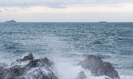 Chapoteo del océano con espuma cerca de rocas grandes Foto de archivo