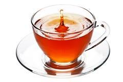 Chapoteo del té en la taza de cristal aislada Imagen de archivo