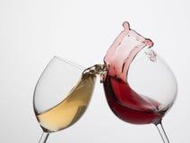 Chapoteo del vino blanco rojo y Imagenes de archivo