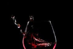 Chapoteo del vino en el vidrio en backround oscuro Imágenes de archivo libres de regalías