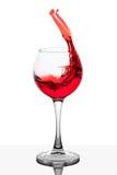 Chapoteo del vino rojo en el relleno de la taza Foto de archivo
