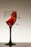 Chapoteo del vino rojo en un vidrio Foto de archivo libre de regalías
