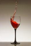 Chapoteo del vino rojo en un vidrio Imagen de archivo