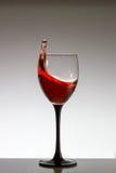 Chapoteo del vino rojo en un vidrio Fotos de archivo