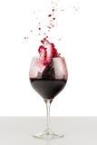 Chapoteo del vino rojo en una copa. Fotos de archivo