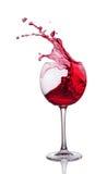 Chapoteo del vino rojo en vidrio imagenes de archivo