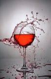Chapoteo del vino rojo en vidrio imagen de archivo
