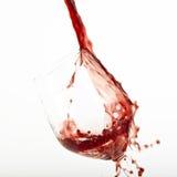 Chapoteo del vino rojo sobre un vidrio. Imagenes de archivo