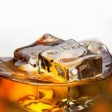 Chapoteo del whisky con el hielo aislado en blanco imagen de archivo