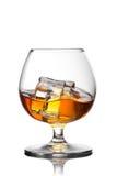 Chapoteo del whisky con hielo en vidrio Fotografía de archivo libre de regalías