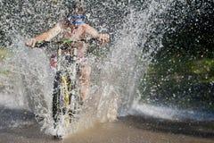 Chapoteo en declive de la bici del agua de Mountainbiker fotografía de archivo libre de regalías