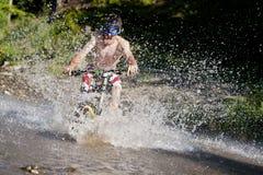 Chapoteo en declive de la bici del agua de Mountainbiker foto de archivo