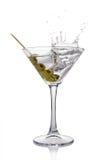 Chapoteo en el vidrio de martini de la bebida alcohólica transparente blanca del cóctel con la aceituna Imagen de archivo libre de regalías