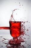 Chapoteo en vidrio de vino reflexionado sobre imagenes de archivo