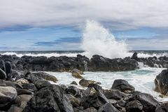 Chapoteo hermoso de un quebrado en las ondas de las rocas volcánicas foto de archivo