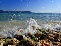Chapoteo hermoso del agua en la orilla de mar de la roca en el lado de la playa fotos de archivo libres de regalías