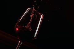 Chapoteo rojo de la copa de vino en fondo negro Fotografía de archivo libre de regalías