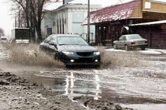 Chapoteo sucio del agua de las ruedas de coche en la calle nevosa de la primavera Imagenes de archivo