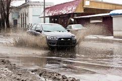 Chapoteo sucio del agua de las ruedas de coche en la calle nevosa de la primavera Fotografía de archivo libre de regalías
